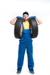 Tire service worker in blue uniform holds car tyre