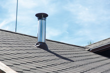 Chimney Pipe From Stainless Steel On The Roof Of The House.