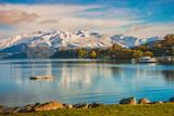 Poranny śnieg nad jeziorem Wanaka, wyspa południowa, Nowa Zelandia z widokiem na śnieżną górę, kolorowe drzewo jesienią, jezioro i błękitne niebo