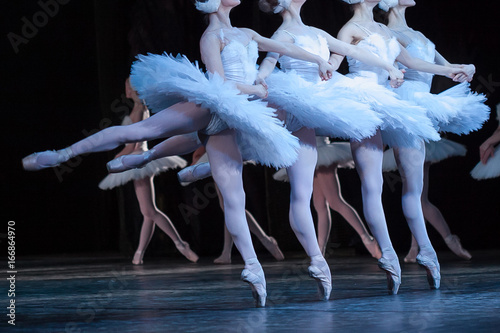 Photo sur Toile Cygne beauty, agility, dancing concept. arm in arm four elegant and graceful female ballet dancers, playing the roles of petite swans, moving, dancing and jumping synchronously
