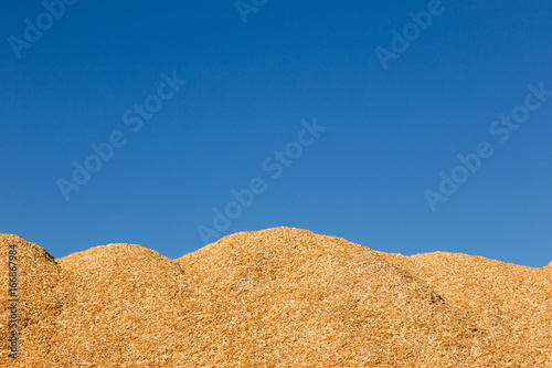 Fotografie, Obraz  Mountain of sawdust Against the blue sky