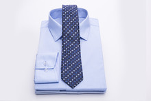 Three Blue Men's Shirts Folded In A Pack And Tie On A White Background.
