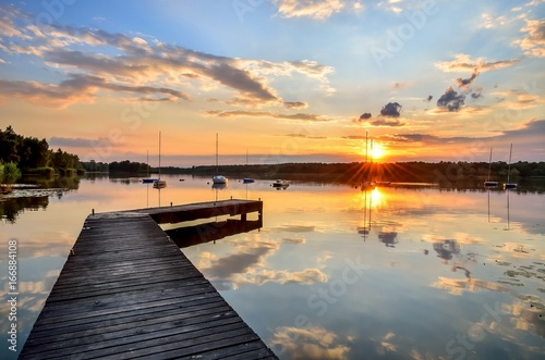 Summer afternoon landscape. Wooden pier and boat on the water at sunset.