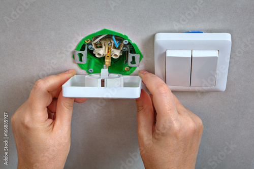 Fixing electrical wall outlet and light switch,  electrician hands close-up.