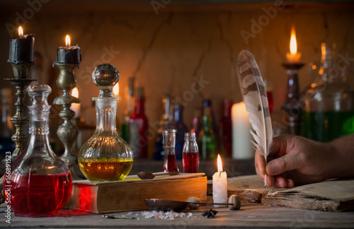Fototapeta hand, magic potion, ancient books and candles obraz