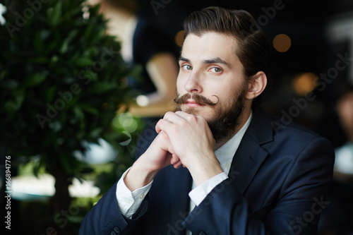 Serious and elegant entrepreneur with curled moustache looking at camera Wallpaper Mural