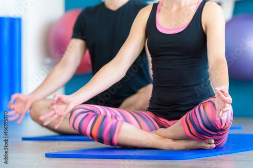 Fotobehang School de yoga Nice couple doing yoga in a studio. Young people in yoga class in lotus position. Yoga group concept.