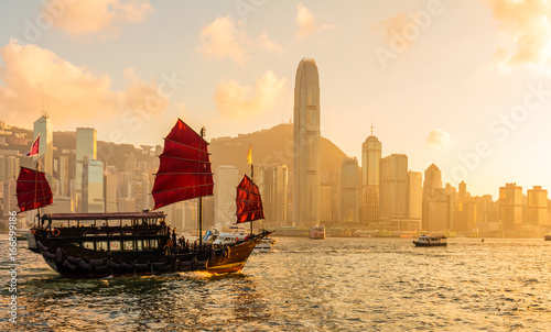 Photographie Chinese wooden red sails ship in Hong Kong Victoria harbor at sunset time