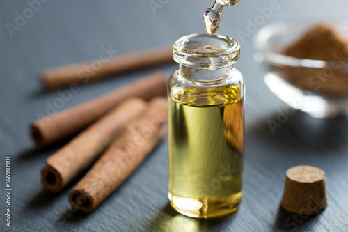 Tableau sur Toile A drop of cinnamon essential oil is being dropped into a bottle