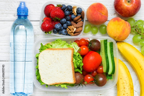 Papiers peints Assortiment School lunch boxes with sandwich, fresh fruits and vegetables, berries and nuts and bottle of water