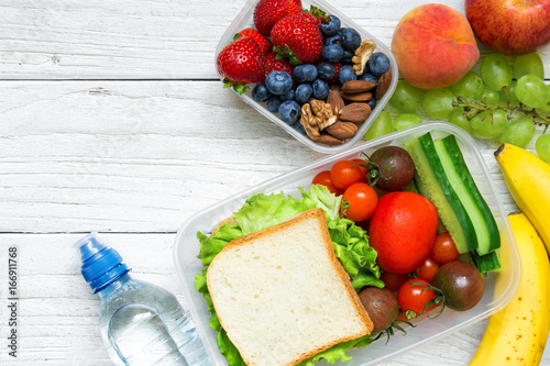 Foto op Aluminium Assortiment School lunch boxes with sandwich, fruits, vegetables and bottle of water and copy space