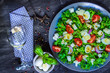 Salad of fresh vegetables and a glass of wine on a black wooden background.