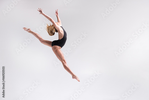 Spoed Fotobehang Gymnastiek Pensive young girl doing gymnastics leap