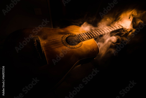 Obraz Music concept. Acoustic guitar isolated on a dark background under beam of light with smoke with copy space. Guitar Strings, close up. Selective focus. Fire effects - fototapety do salonu