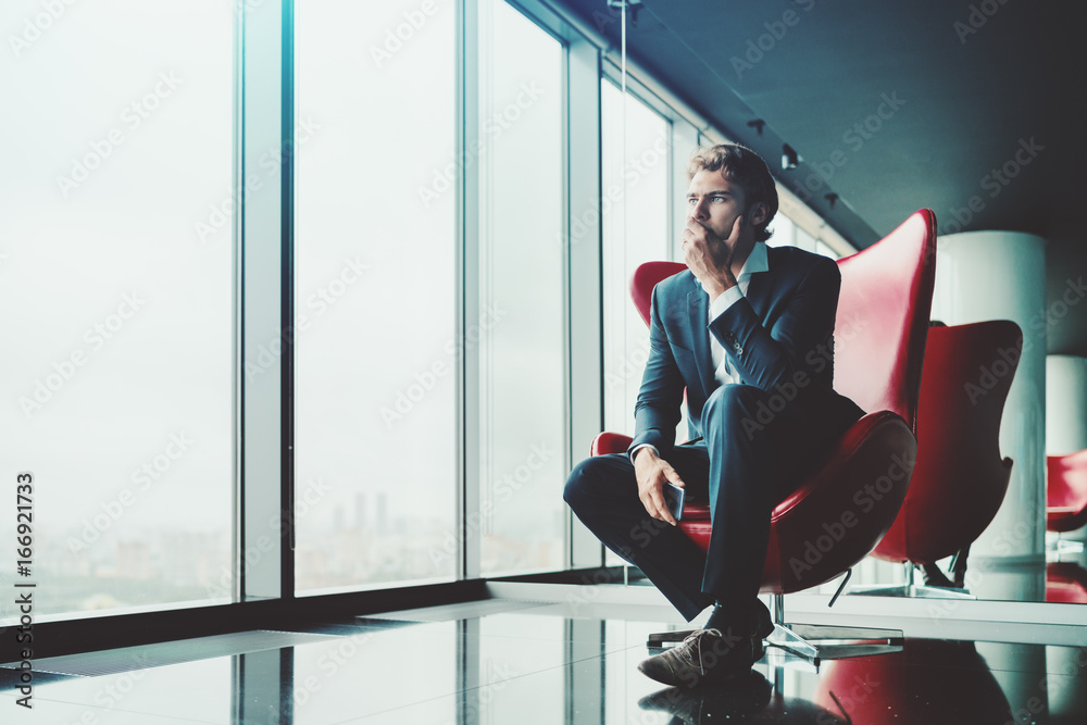 Fototapeta Adult pensive and anxious businessman in blue formal suit is sitting on red armchair in luxury office interior near window and recapitulating recent work meeting with copy space zone for advertising