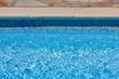 Pool side with blue tiles and clear water