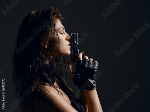 фотография  Closeup portrait of beautiful sexy brunette woman with old revolver gun