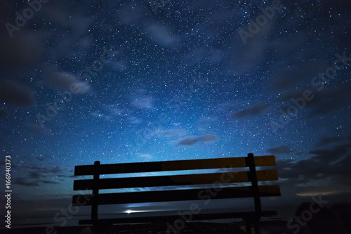 Wooden Park Bench Silhouetted In Front Of View Of Night Sky Full Of