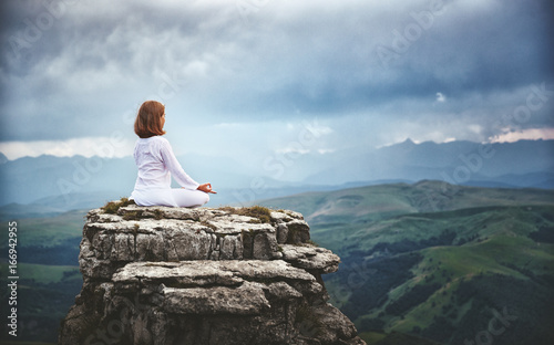 woman practices yoga and meditates in   lotus position on mountains, peak Canvas Print