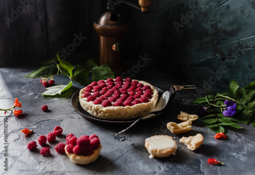 raspberry tart with fresh beries on old black pan with coffee grinder, spoon. flowers and crushed tart on a grey background