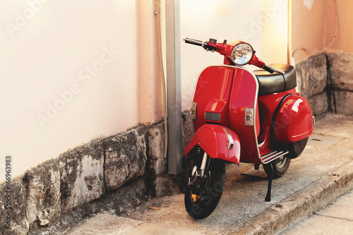 Deurstickers Scooter Red vintage scooter parked near a building wall - outdoors shot