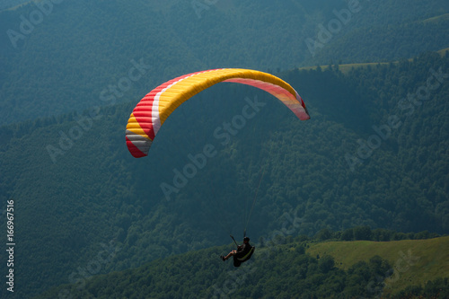 Fotografie, Obraz  A paraglider flies over a mountain valley on a sunny summer day