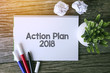 Action Plan 2018 word with Notepad and green plant on wooden background.