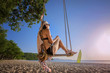 woman in bikini sitting relax on wooden swing at sea beach on the sunlight