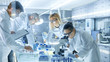 canvas print picture - Team of Medical Research Scientists Work on a New Generation Disease Cure. They use Microscope, Test Tubes, Micropipette and Writing Down Analysis Results. Laboratory Looks Busy, Bright and Modern.