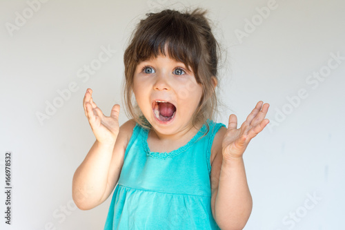 Valokuva  Surprised Cute child holding hands in surprised gesture, keeping mouth wide open