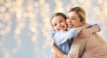 Happy Girl With Mother Hugging Over Lights
