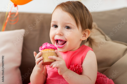 happy baby girl eating cupcake on birthday party Canvas Print
