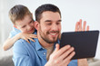 father and son with tablet pc having video chat