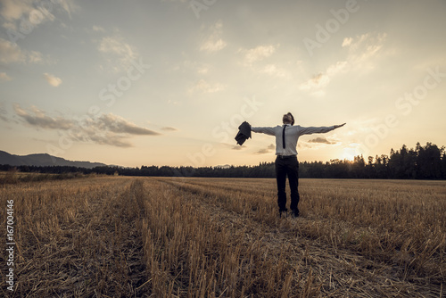Foto  Retro image of a successful young businessman standing at the field