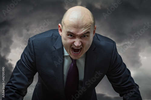 Fotografiet  Angry boss. Businessman in suit with very angry face screaming.
