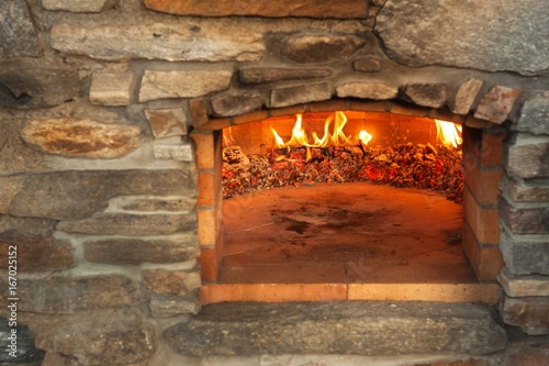 Home outdoor stone pizza oven. Traditional pizza production. Preparation of dinner.