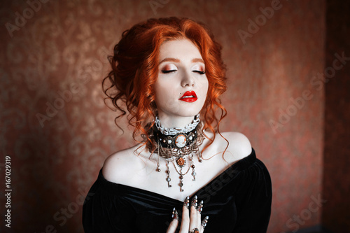 Fotografie, Obraz  A woman is a vampire with pale skin and red hair in a black dress and a necklace on her neck