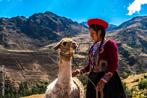 Fotobehang Lama Native Peruvian girl with her lama animal in Sacred Valley, Cusco, Peru