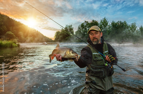 Acrylic Prints Fishing Sport fisherman holding trophy fish. Outdoor fishing in river