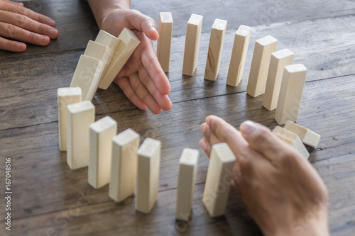 Fotografía  Hand stopping domino effect of wooden blocks for concept about business and accountability