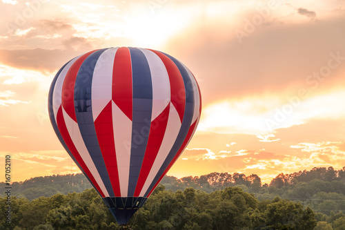 Fotografie, Obraz  Hot air balloon in red, white and blue floats among the mountains in a beautiful