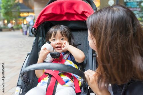 若い母親と乳母車に乗った娘