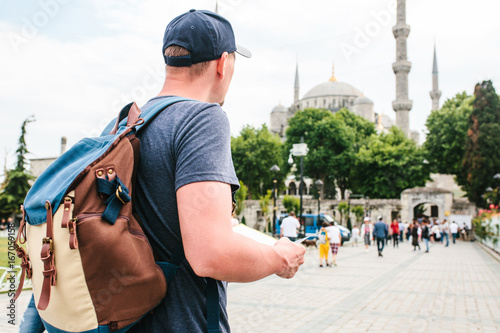 Fotografering  A traveler in a baseball cap with a backpack is looking at the map next to the blue mosque - the famous sight of Istanbul