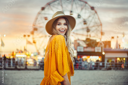 Foto op Plexiglas Amusementspark Beautiful exited smiling tourist woman having fun at amusement park at hot summer day trip on the beach.