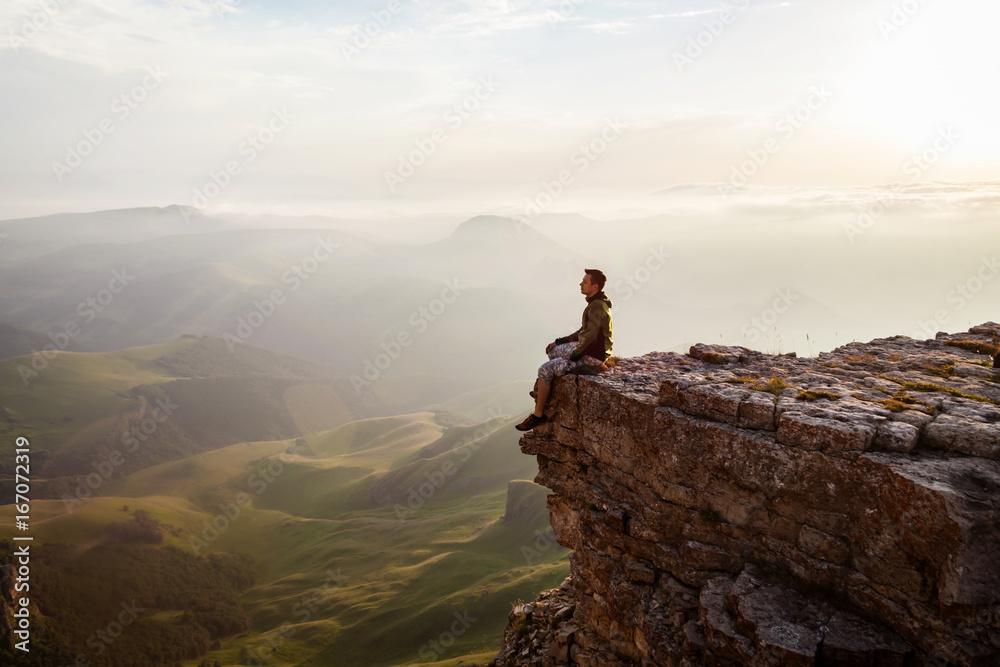 Fototapety, obrazy: Man sitting on the cliff and enjoying sunset