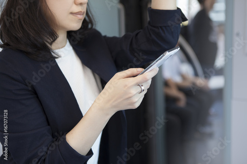 A woman is caught on a hanging leather inside a train and watching a smartphone