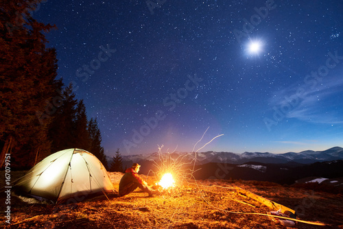 Male tourist have a rest in his camp at night, sitting near campfire and tent under beautiful night sky full of stars and the moon and enjoying night scene in the mountains