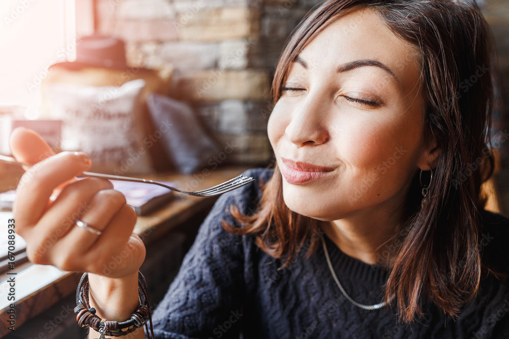 Fototapeta beautiful young asian woman sitting in a cafe and eating delicious cake