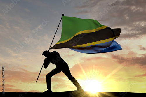 Poster Superheroes Tanzania flag being pushed into the ground by a male silhouette. 3D Rendering