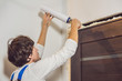 Young handyman installing door with an mounting foam in a room
